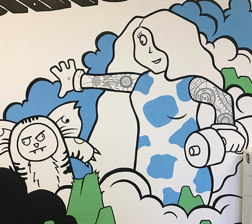 Closeup of the strength shack mural looking at a dropbear and s tattooed female lifting a weight