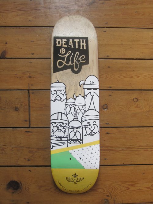 """Picture of up-cycled skate board deck with vikings and the phrase""""Death is Life"""" painted on it."""
