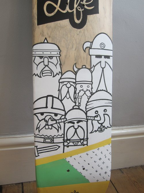 """Close up of up-cycled skate board deck with vikings and the phrase""""Death is Life"""" painted on it."""