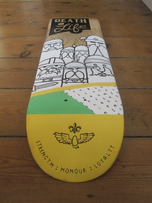 """Close up of up-cycled skate board deck with vikings and the phrase""""Strength, honour and loyalty"""" painted on it."""